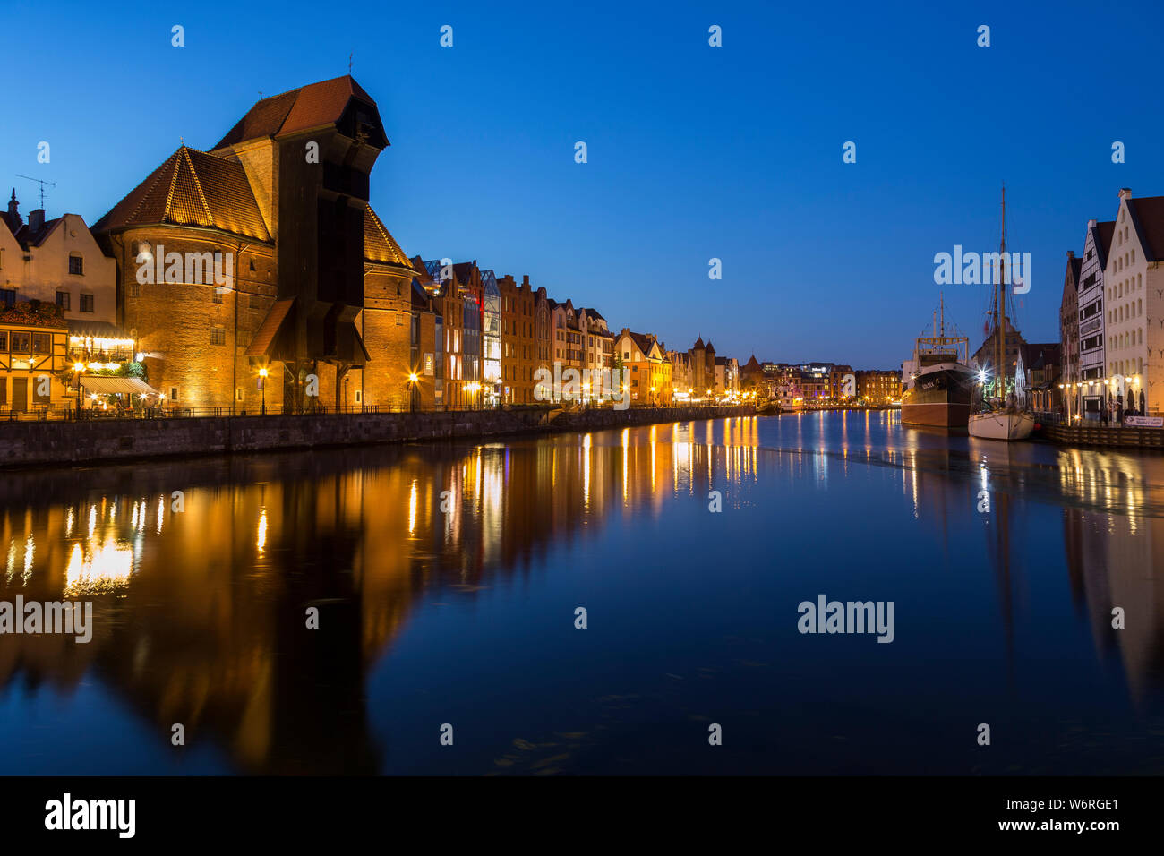 Scenic view of the lit Crane and other old buildings along the Long Bridge waterfront at the Main Town in Gdansk, Poland, in the evening. Stock Photo