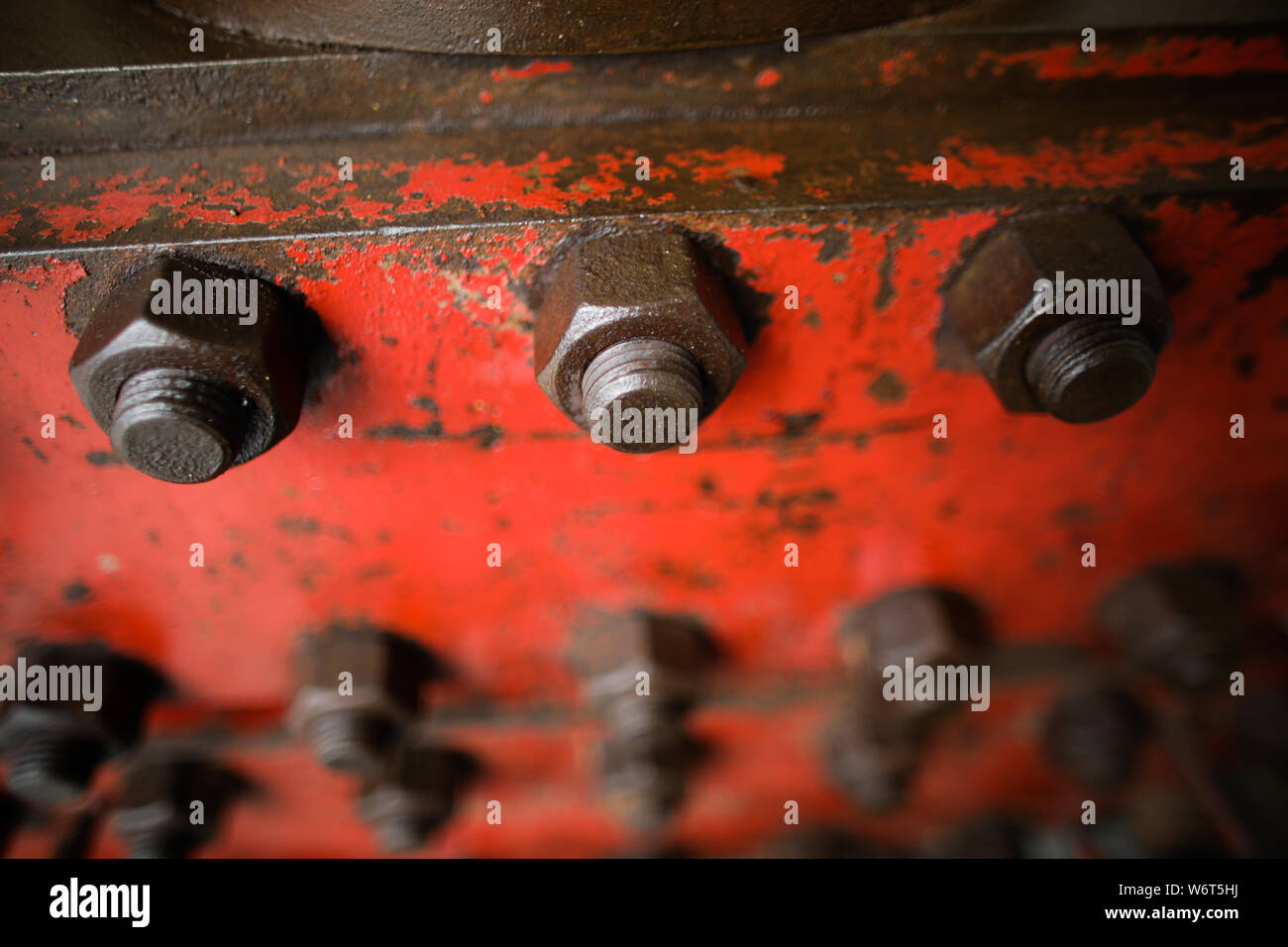 Shallow depth of field image with worn out heavy iron industrial equipment used in the oil and gas drilling industry (rusty bolts, nuts, pipes, levers Stock Photo