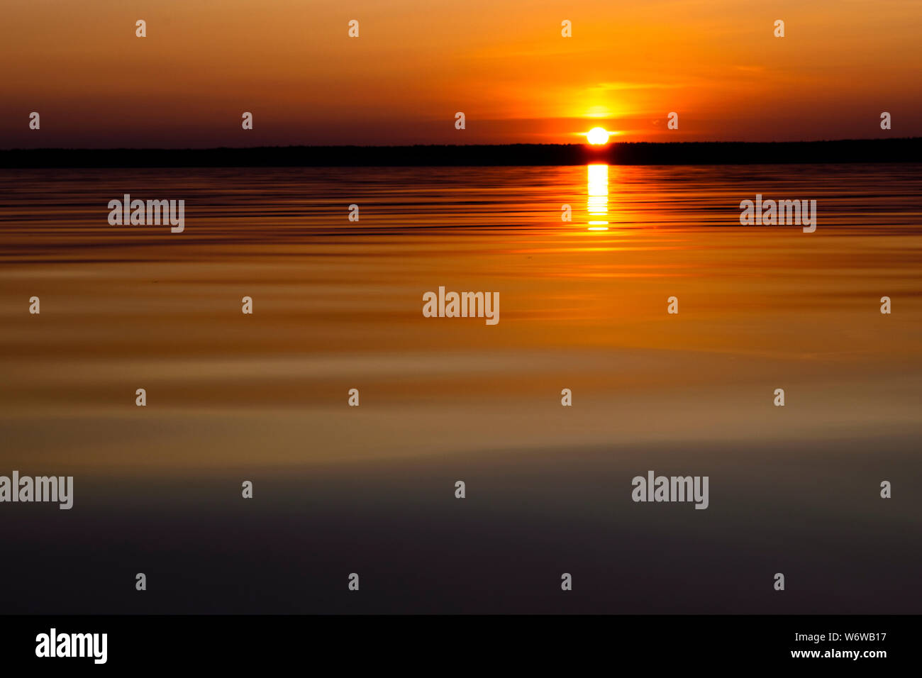 Water surface. View of a Sunset sky background. Dramatic gold sunset sky with evening sky clouds over the sea. View of a Crystal clear sea water textu Stock Photo