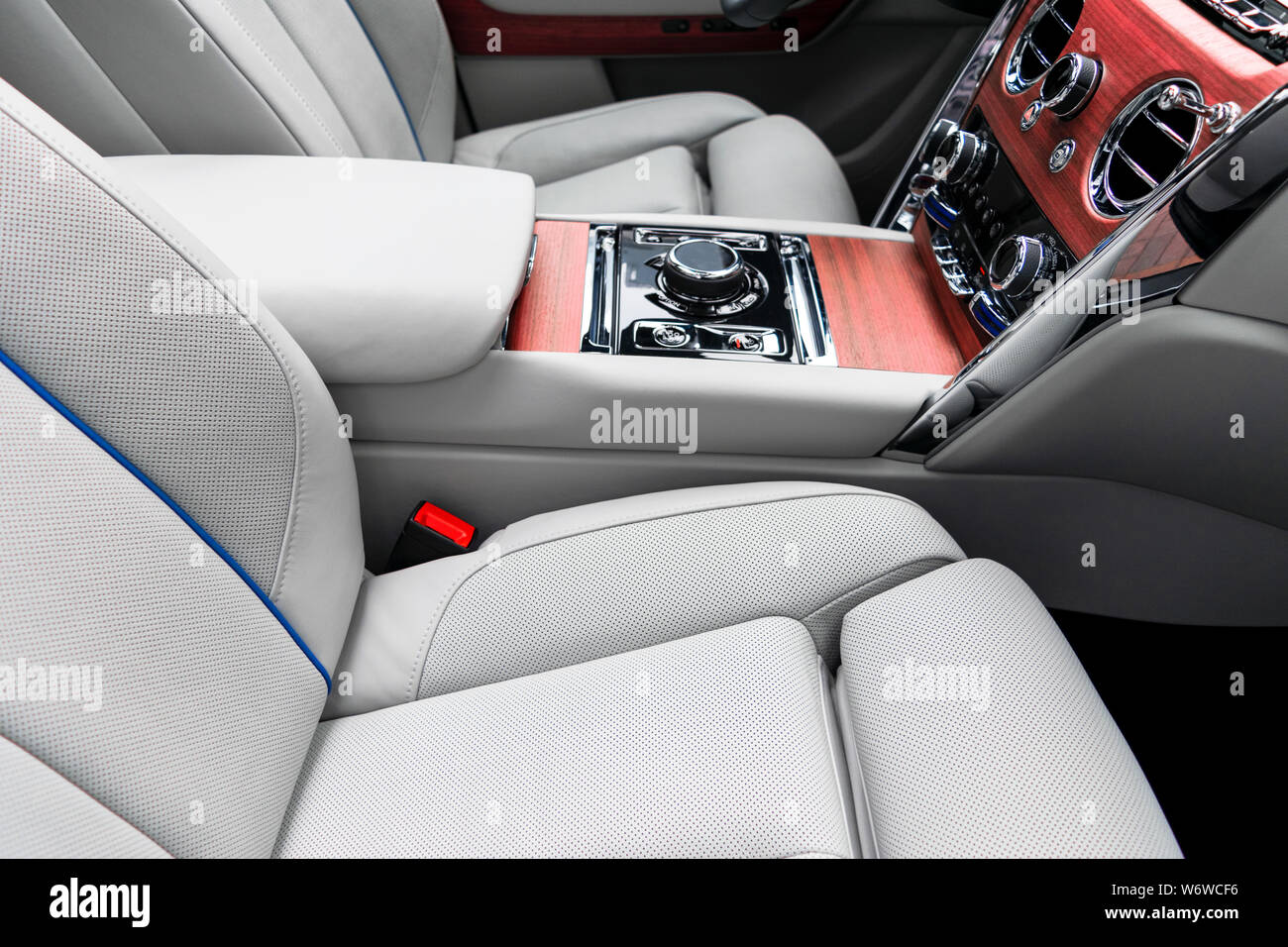 Modern luxury car white leather interior with natural wood panel. Part of leather car seat details with stitching. Interior of prestige modern car. Wh Stock Photo