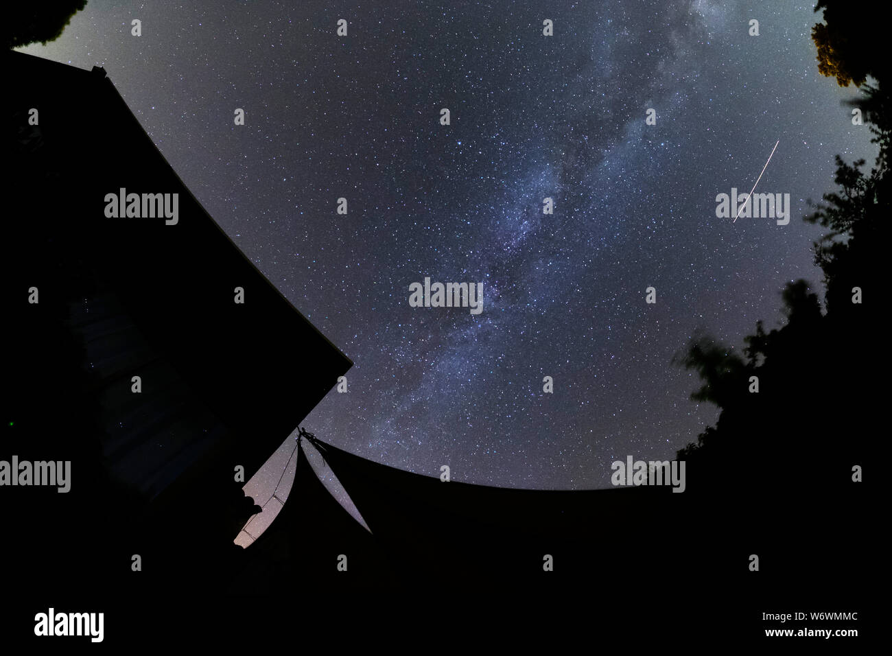 Sablet, The Vaucluse, France. 3rd August 2019. Clear dark skies in southern France show the Milky Way appearing brightly in the night sky with a bright satellite trail running parallel to the galactic plane. Credit: Malcolm Park/Alamy Live News. Stock Photo