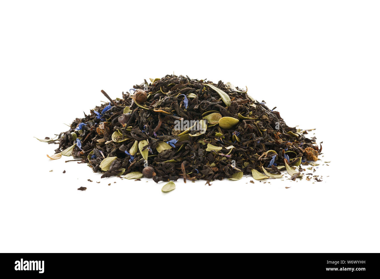Dry black tea mixed with herbs, flower petals and berries on white background. Stock Photo