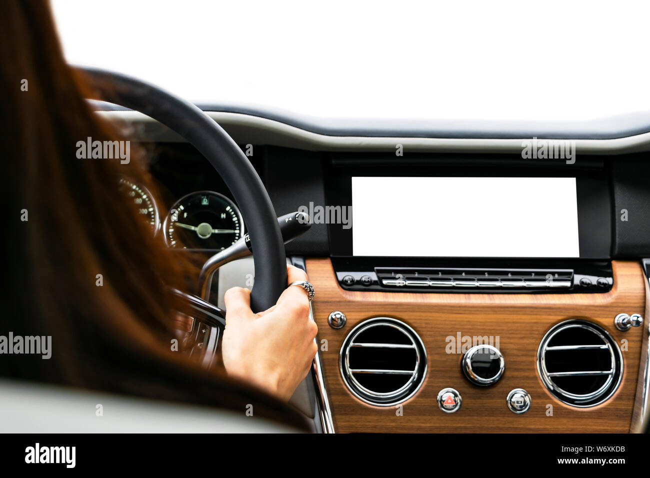 Woman hands holding car steering wheel of a modern car. Hands on steering wheel of a car driving. Girl driving a car inside cabin. Monitor in car with Stock Photo
