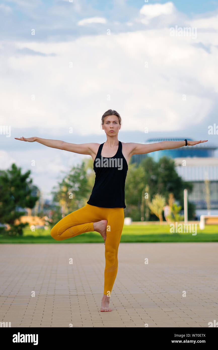 Handsome athletic woman doing yoga asanas in the park. My training is my meditation and my yoga. Woman yoga instructor. Health care. Success in sport. Stock Photo