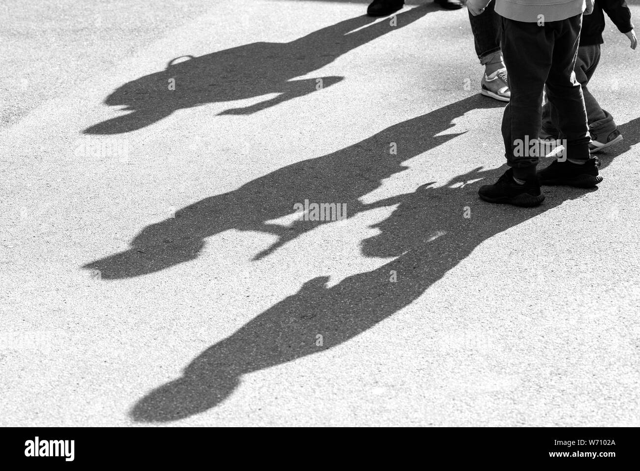 Shadows and Silhouettes of three Children playing in a Street on surface of asphalt Road as Background or Texture Stock Photo