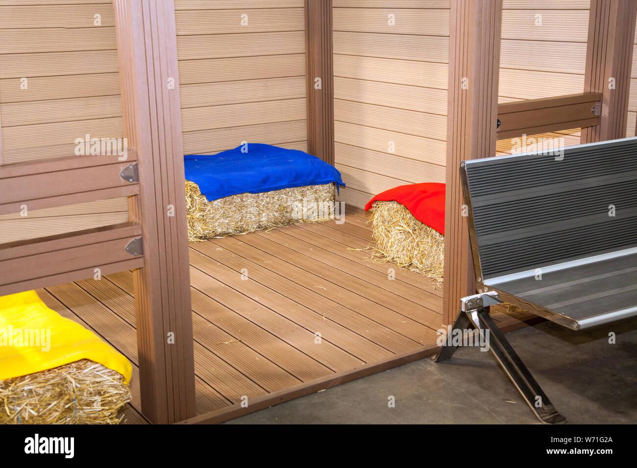 bales of hay on floor near wooden walls Stock Photo
