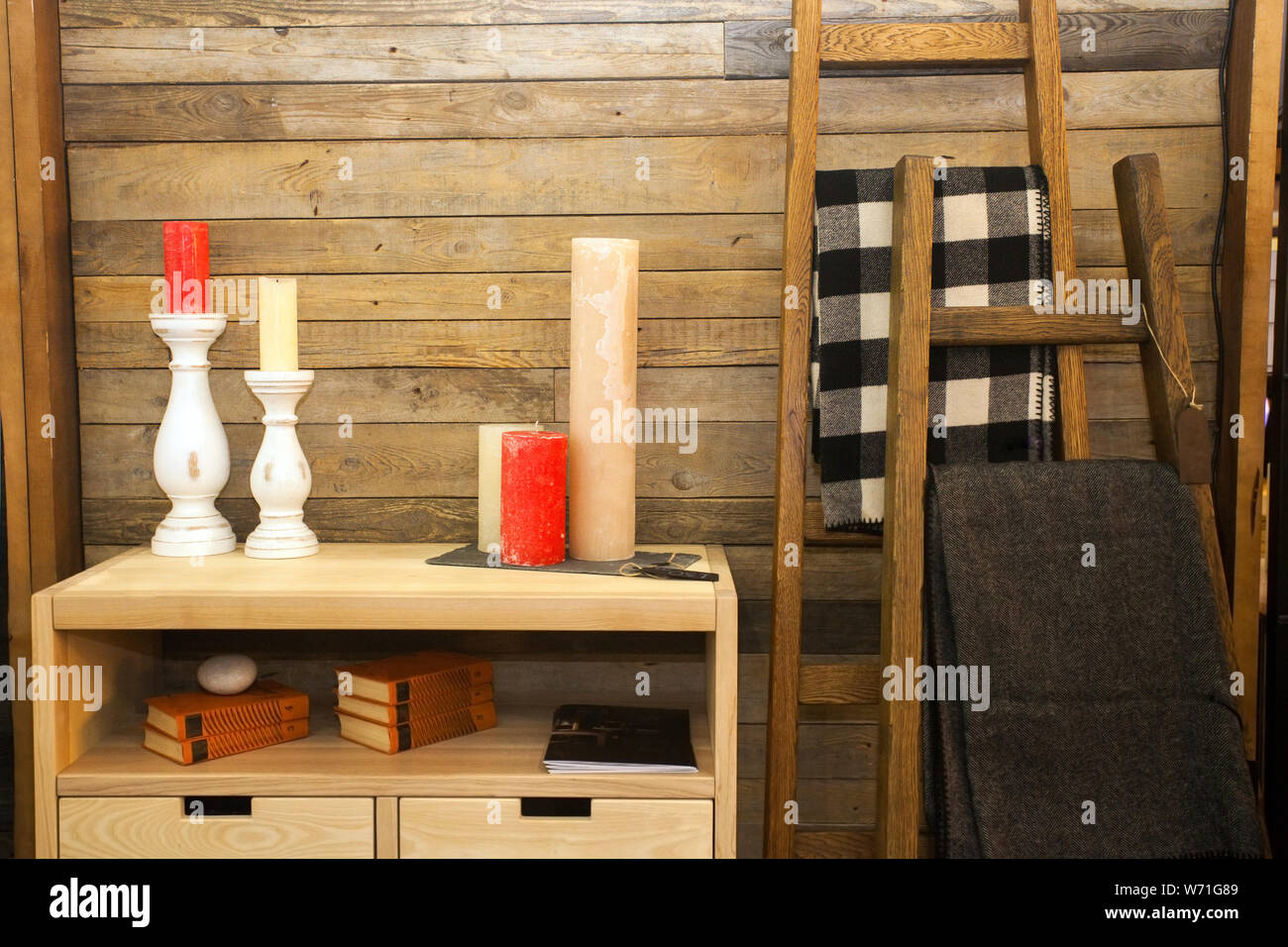 set of colorful candles on wooden chest of drawers near wall at house Stock Photo