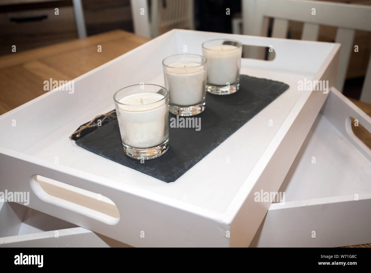 tray with set of candles in glasses on table Stock Photo