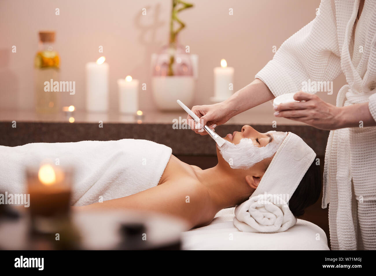 Side view portrait of beautiful mixed race woman enjoying facial therapy in spa, copy space Stock Photo