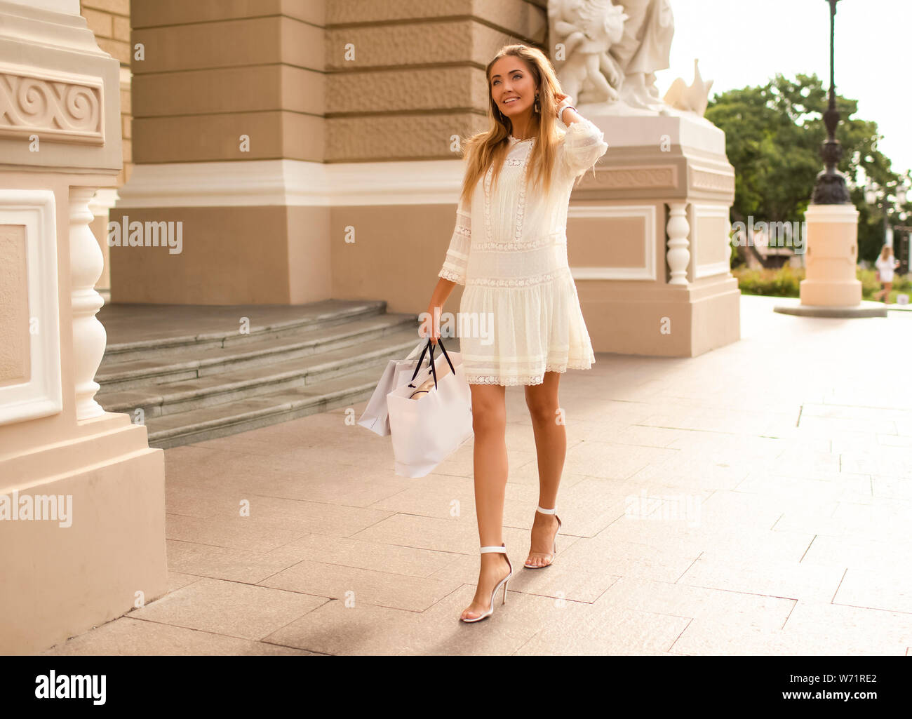 Happy lady walking and shopping in a beautiful city on her vacation. Wearing modern white dress with pattern and high heel shoes with open toes.Makeup Stock Photo