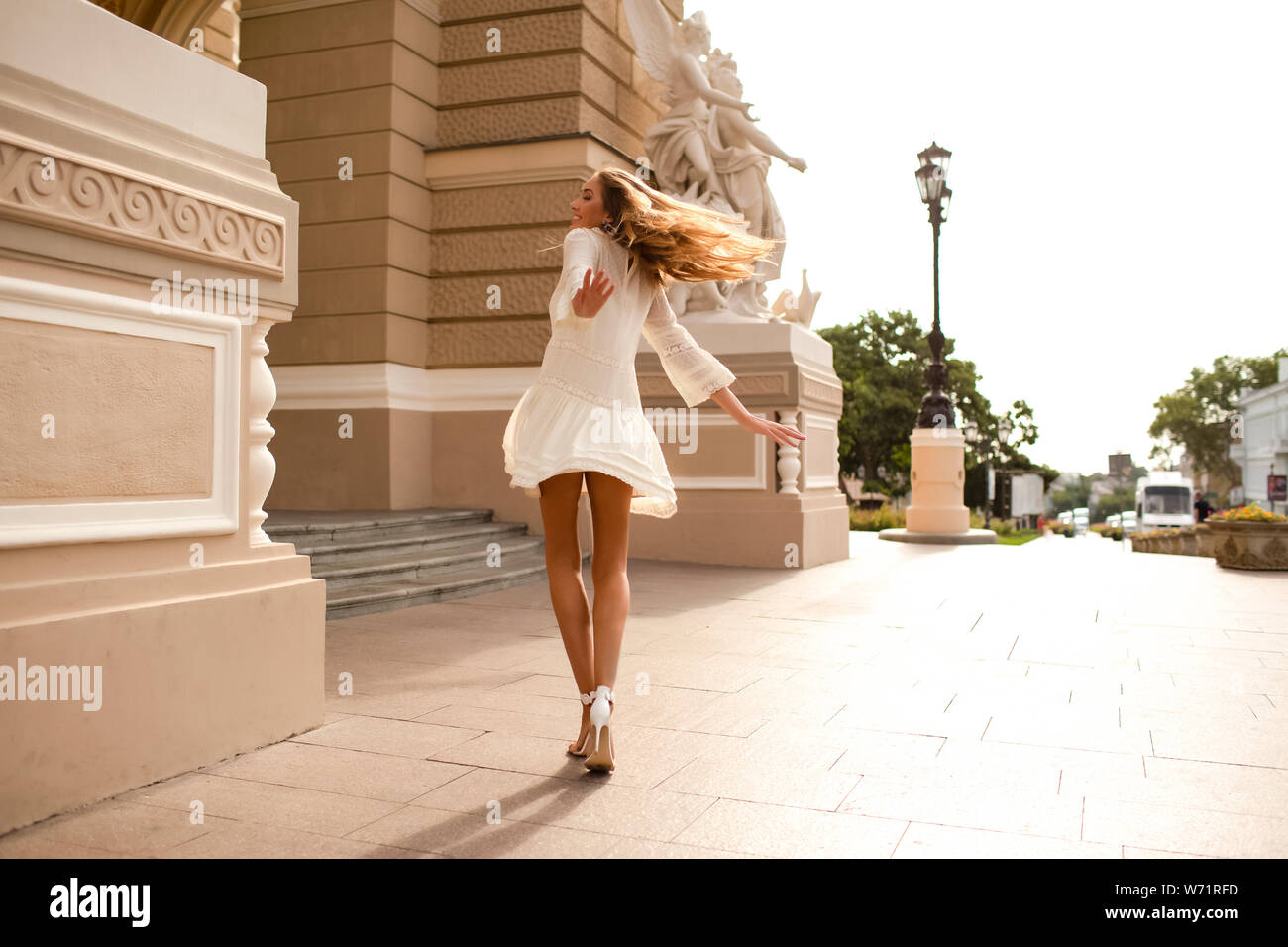 Shining young lady dancing outdoor on the street in the light white dress. Long blonde hair waving, wearing high heel shoes. Happy and funny girl Stock Photo