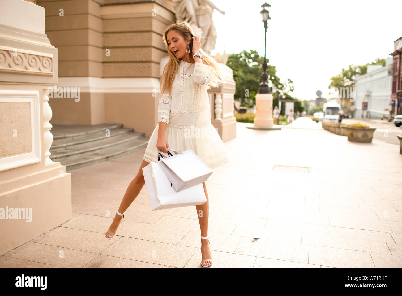 Wonderful woman in a light tender summer collection dress. High heel shoes, amazing slim body. Holding bags with brand new clothes. Long blonde hair l Stock Photo