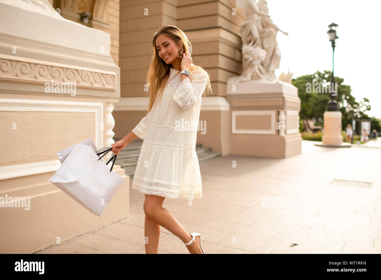 Young model like shopping and buy brand new fashionable clothes. Wearing stylish white summer dress and high heel shoes. Bags with stuff in her hand. Stock Photo