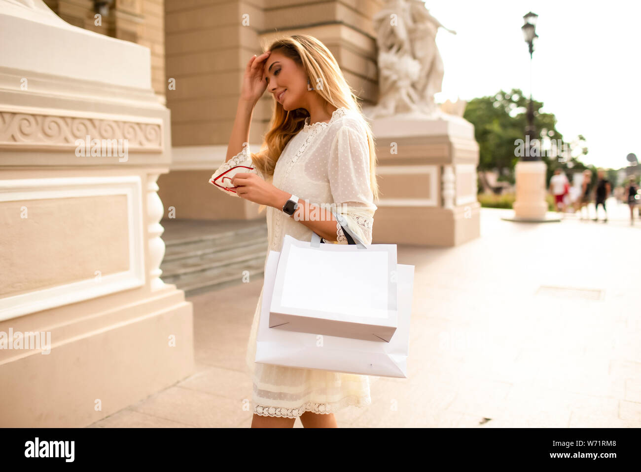 Lovely young female walking on the street and relaxing on summer day. Fashionable look, tender skin. White short dress, watch, stylish hair and makeup Stock Photo