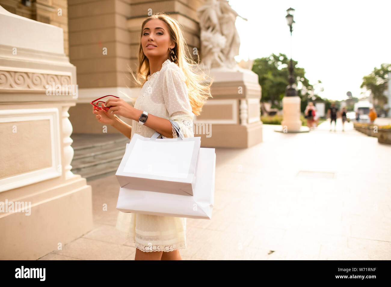 Fashionable lady standing outdoor near the beautiful building with bags on her arm, after a long shopping. She wearing light summer dress and accessor Stock Photo