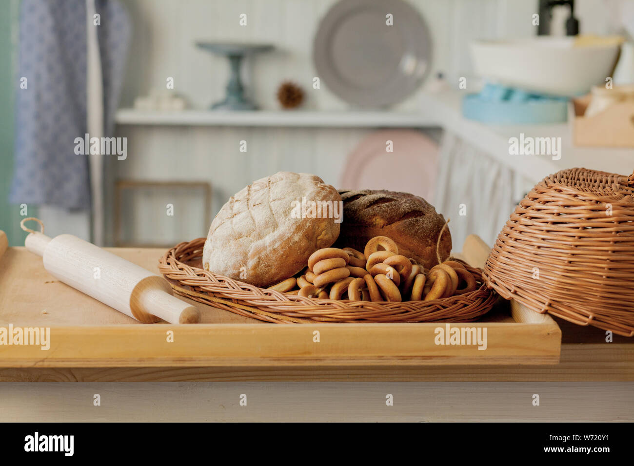 Assortment of breads near a wicker basket on a table in a rustic kitchen. Composition in kitchen at the photo studio. Stock Photo