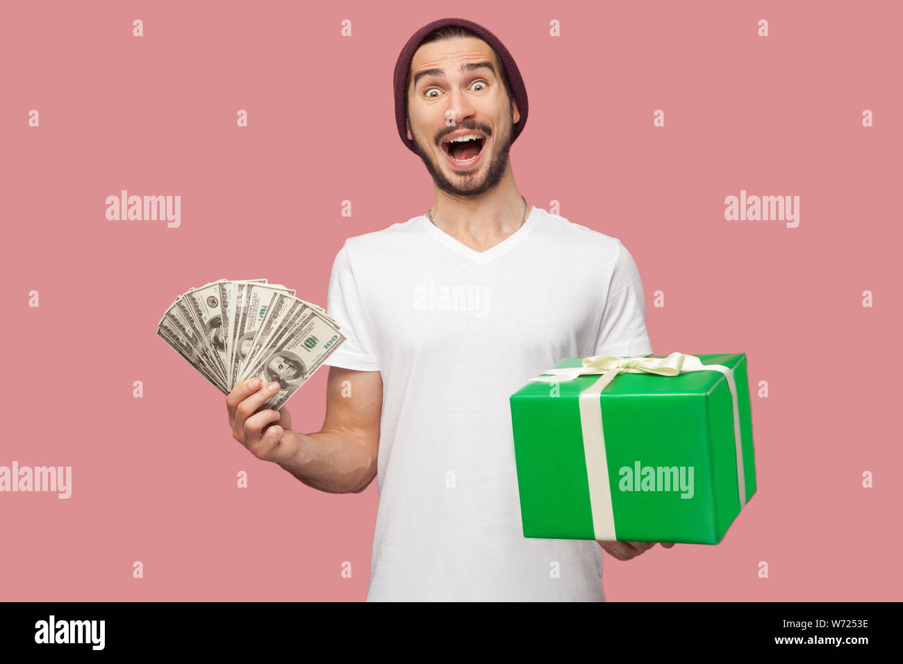 Portrait of suprised handsome bearded young hipster man in white shirt and casual hat standing, holding fan of cash dollars and green present box. Ind Stock Photo