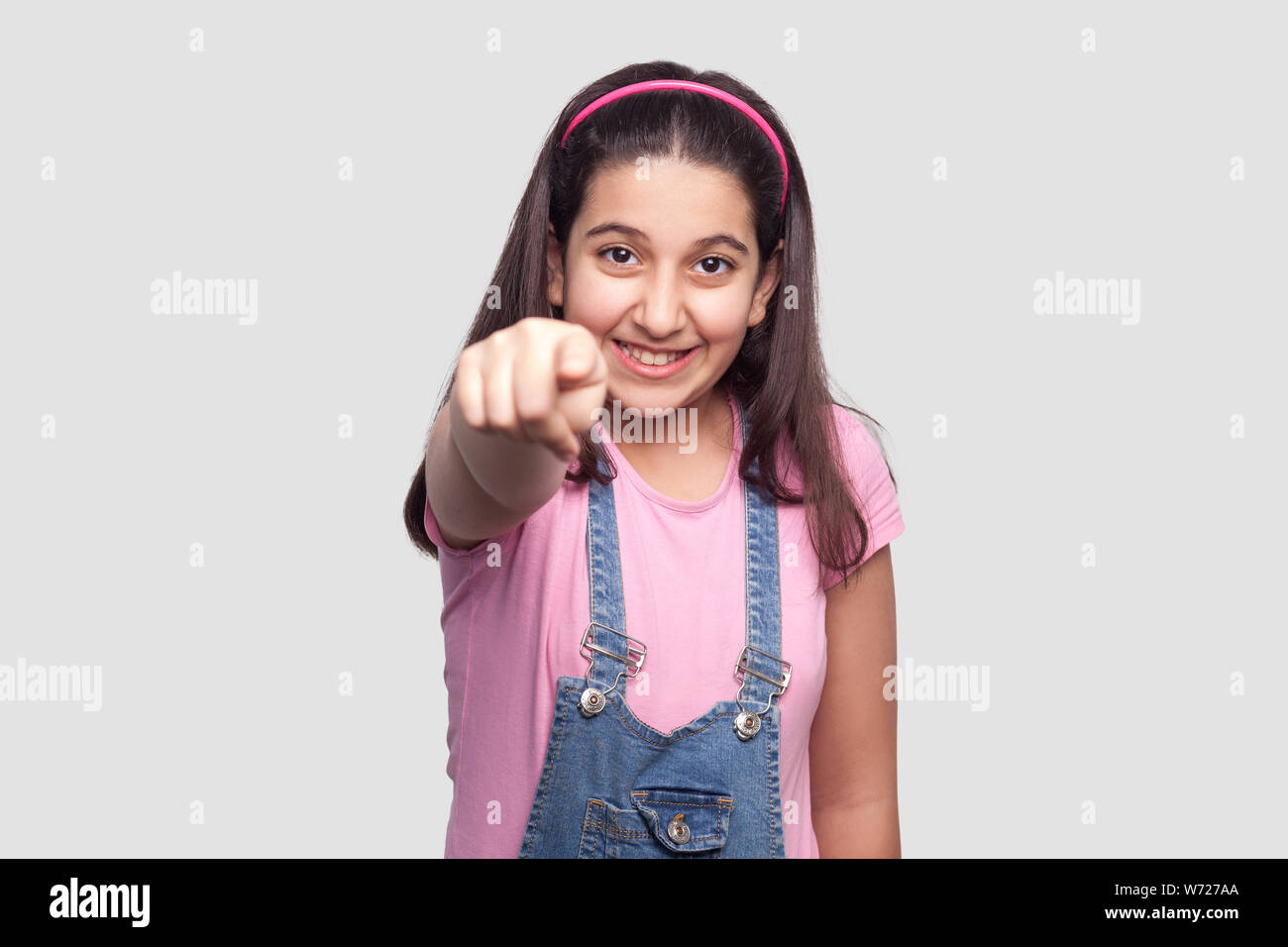 Portrait of happy beautiful brunette young girl in casual pink t-shirt, blue denim overalls standing, looking and pointing at camera with toothy smile Stock Photo