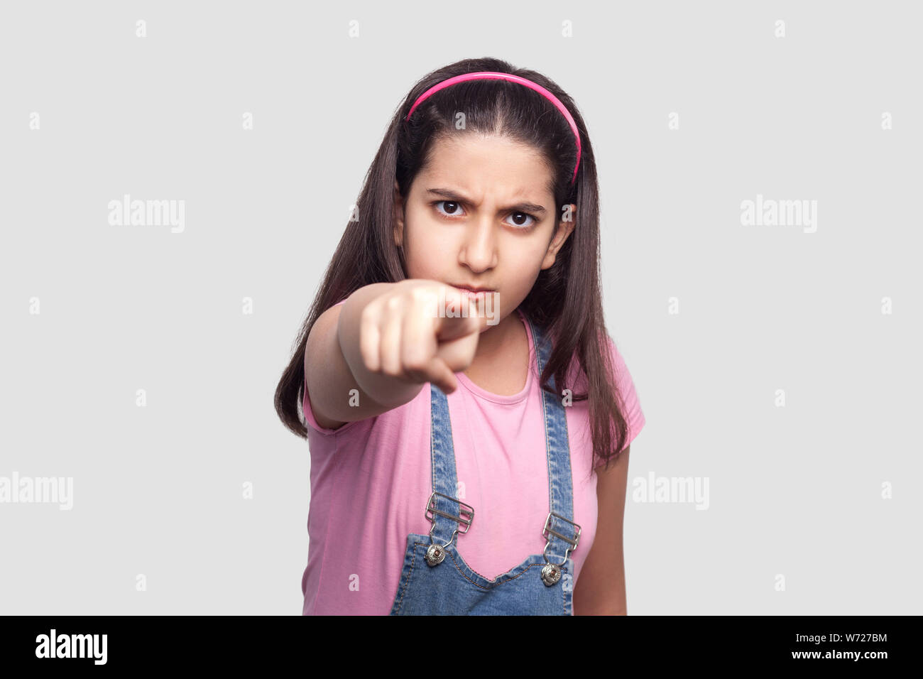 Hey you! Portrait of serious brunette young girl in casual style, pink t-shirt and blue denim overalls standing, blame, looking and accusing at camera Stock Photo