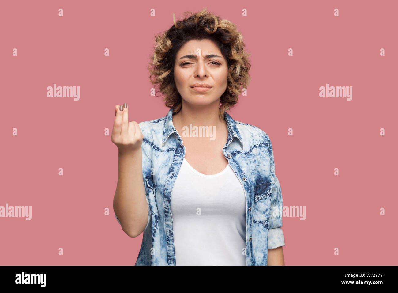 Portrait of serious young woman with curly hairstyle in casual blue shirt standing with money or italian gesture and looking at camera. indoor studio Stock Photo