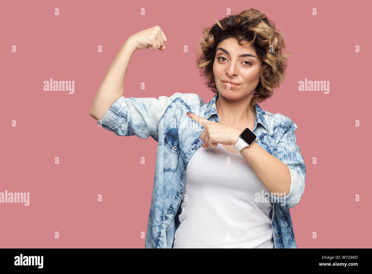Portrait of strong proud young woman with curly hairstyle in casual blue shirt standing and pointing at her biceps to show her independent or feminism Stock Photo