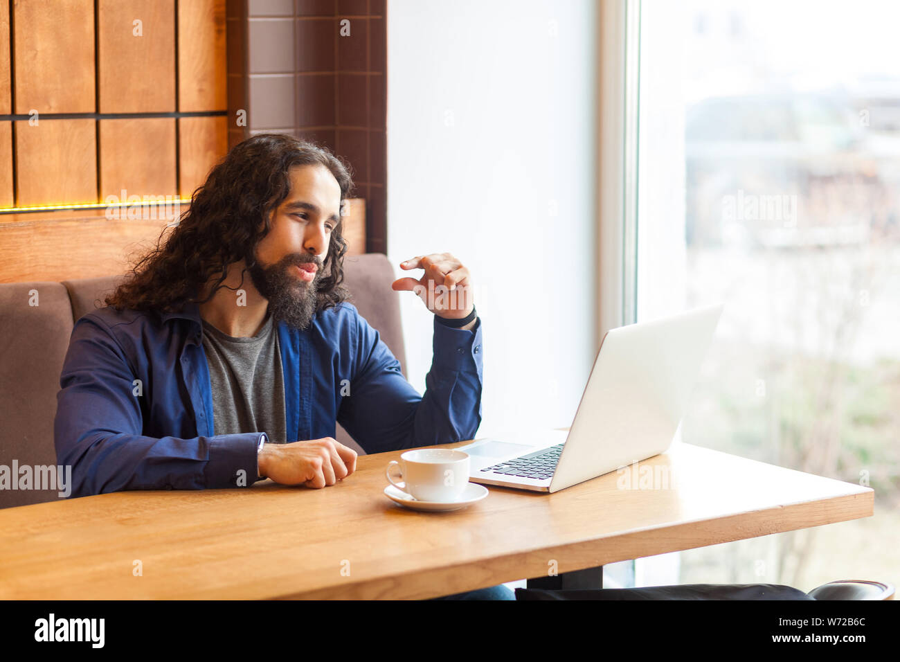 I need more. Portrait of handsome intelligence young adult man freelancer in casual style sitting in cafe and looking at laptop display and asking, bu Stock Photo