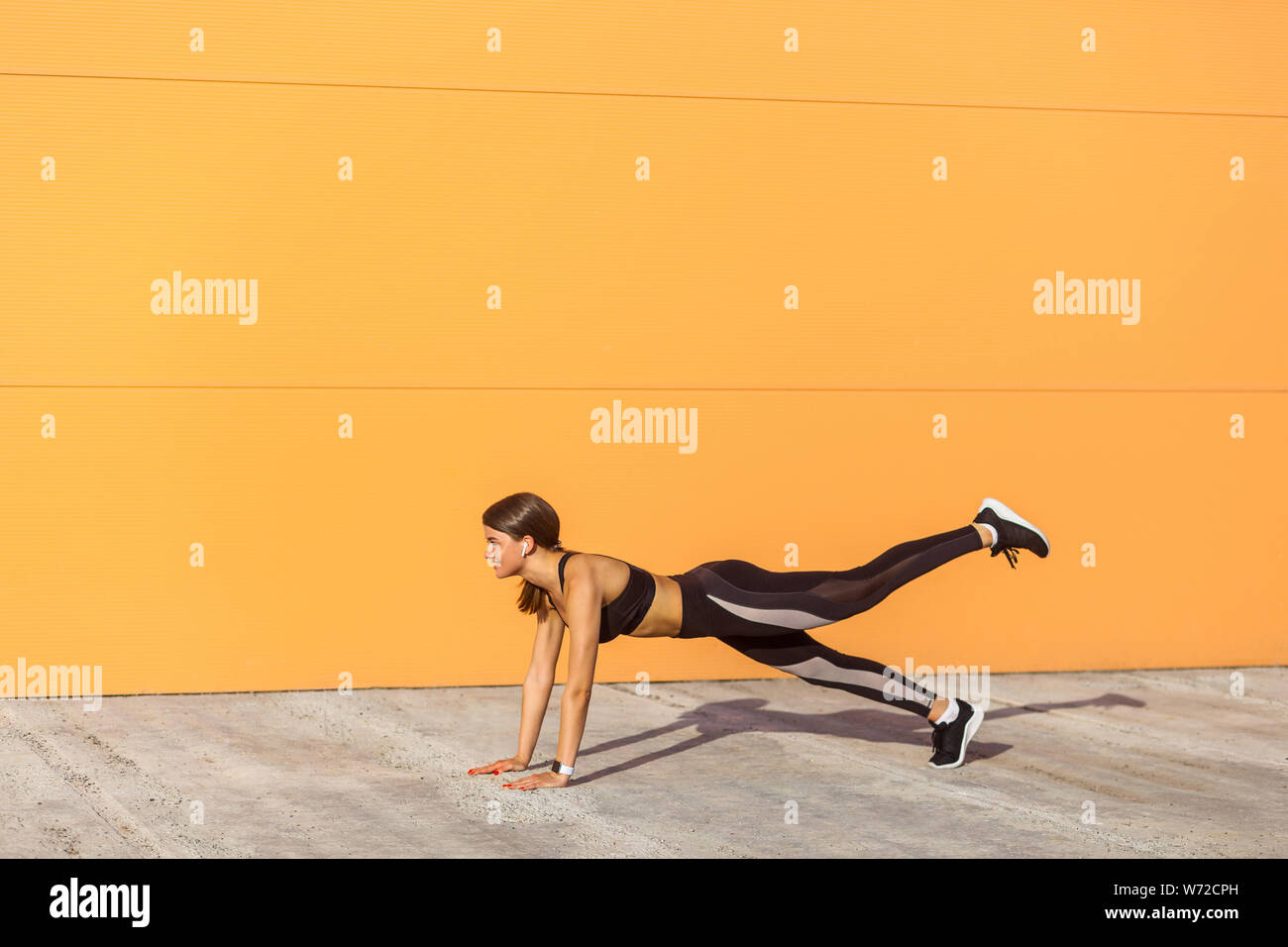 Young satisfied beautiful woman wearing black sporwear practicing sport exercises in morning on street, standing on plank position with raised leg, ho Stock Photo