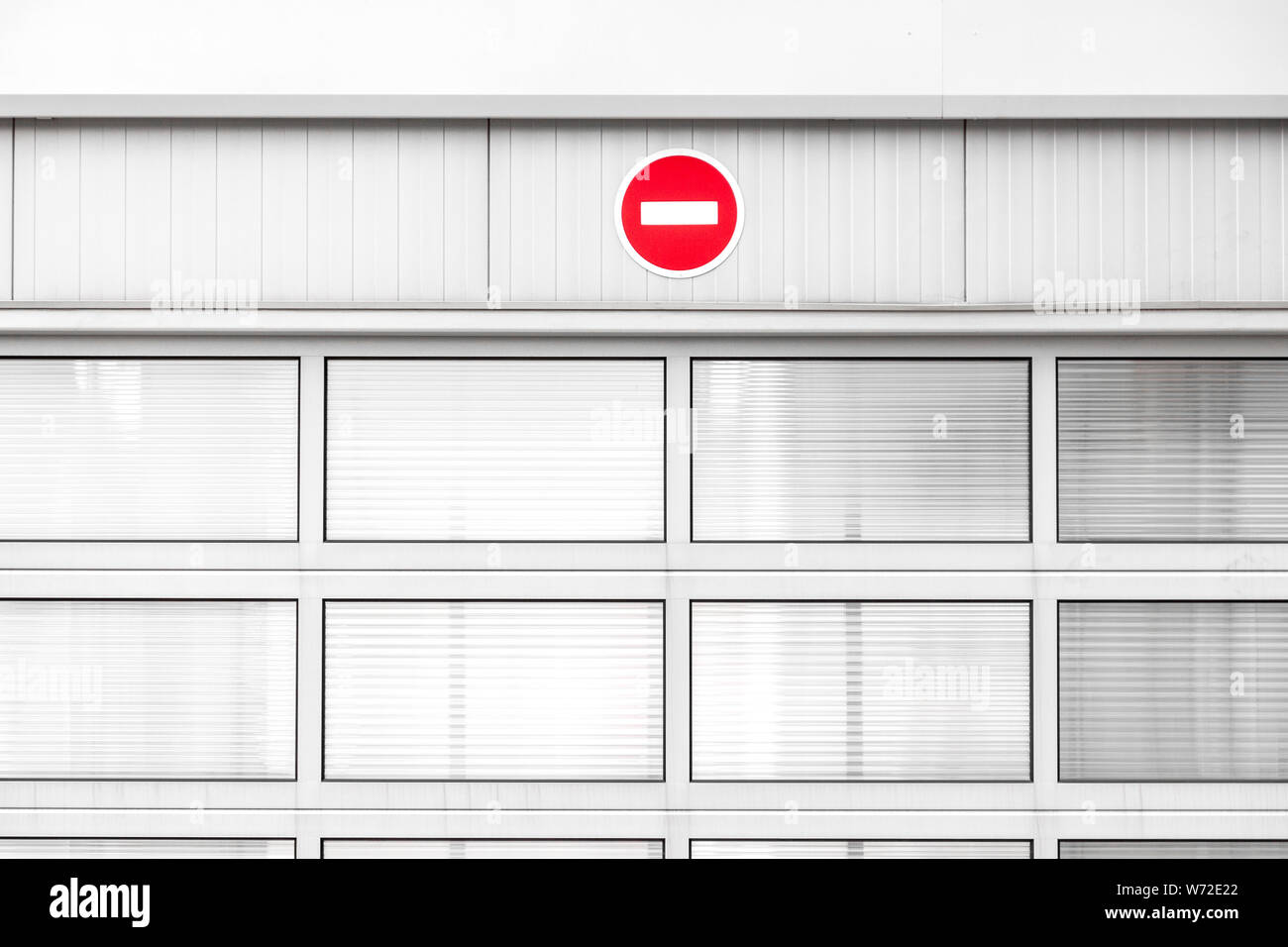 No entry traffic sign on gray industrial wall, minimalist architecture with warning road sign, red color pop up Stock Photo