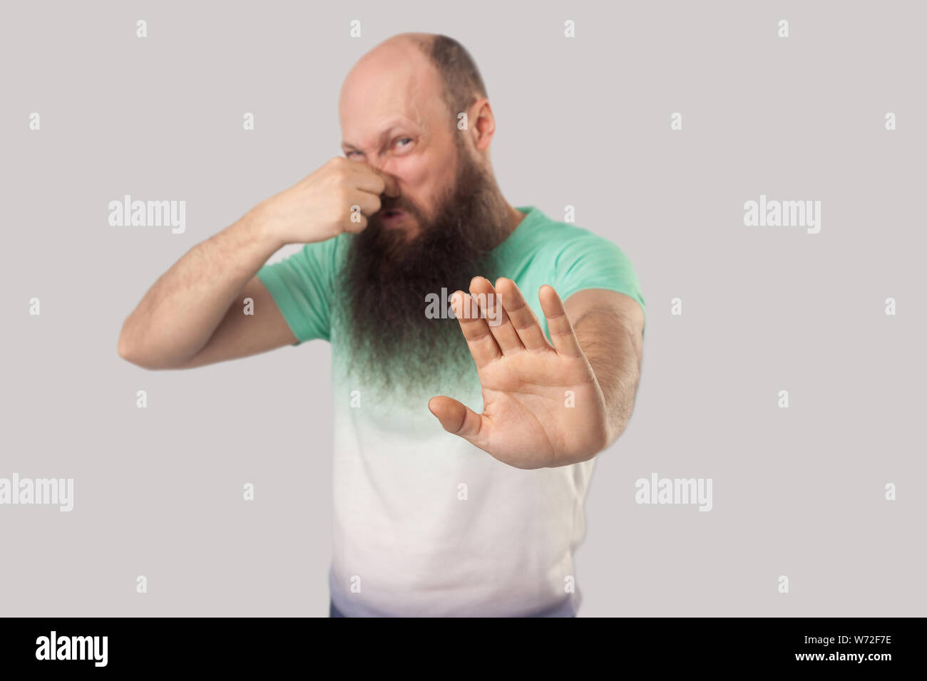 Bad smell, stop. Portrait of confused middle aged bald man with long beard in light green t-shirt standing, blocking his nose and showing stop gesture Stock Photo