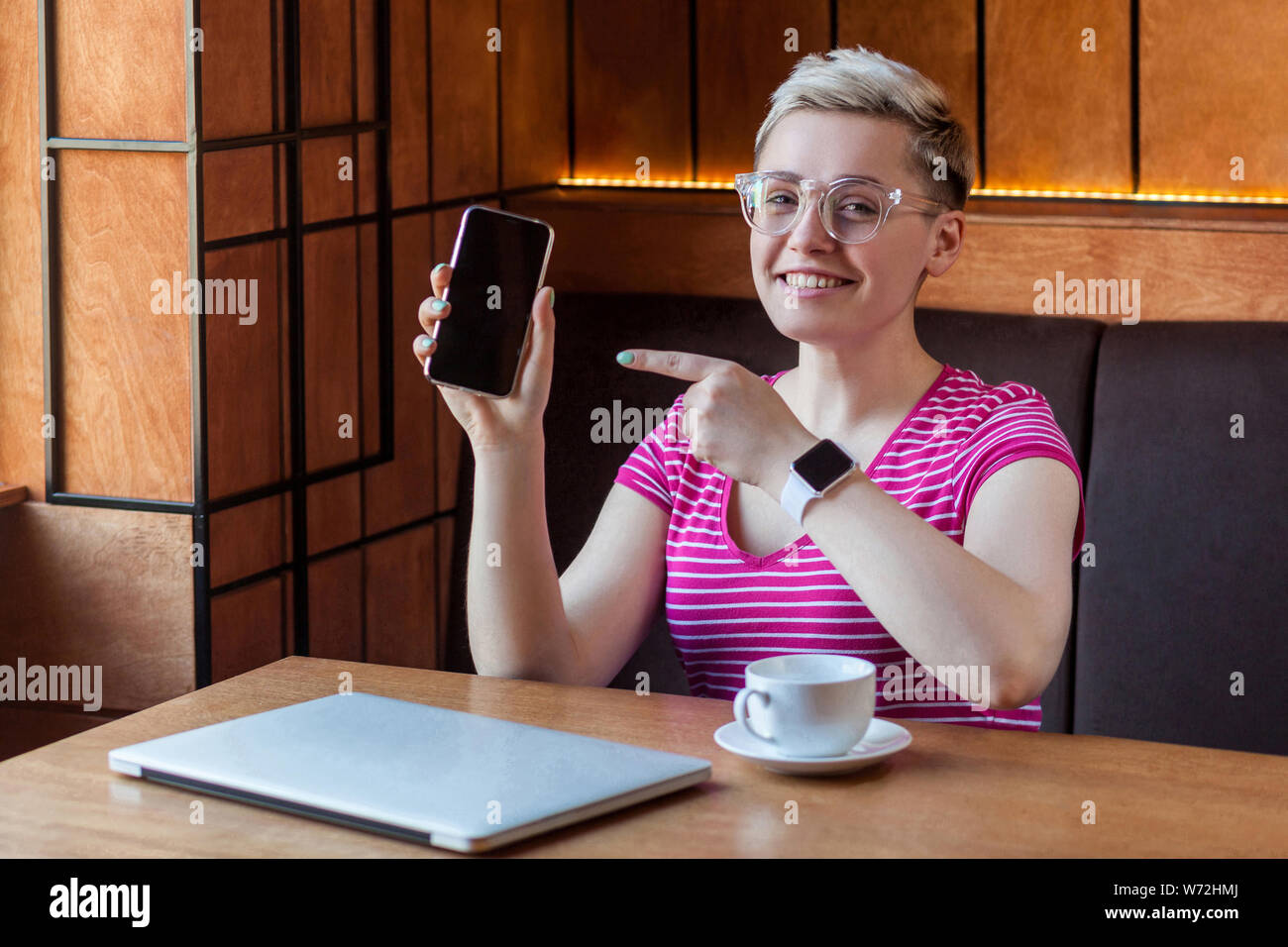 Portrait of beautiful satisfied happy young bussineswoman with blonde short hair in pink t-shirt is sitting in cafe, holding phone and pointing finger Stock Photo