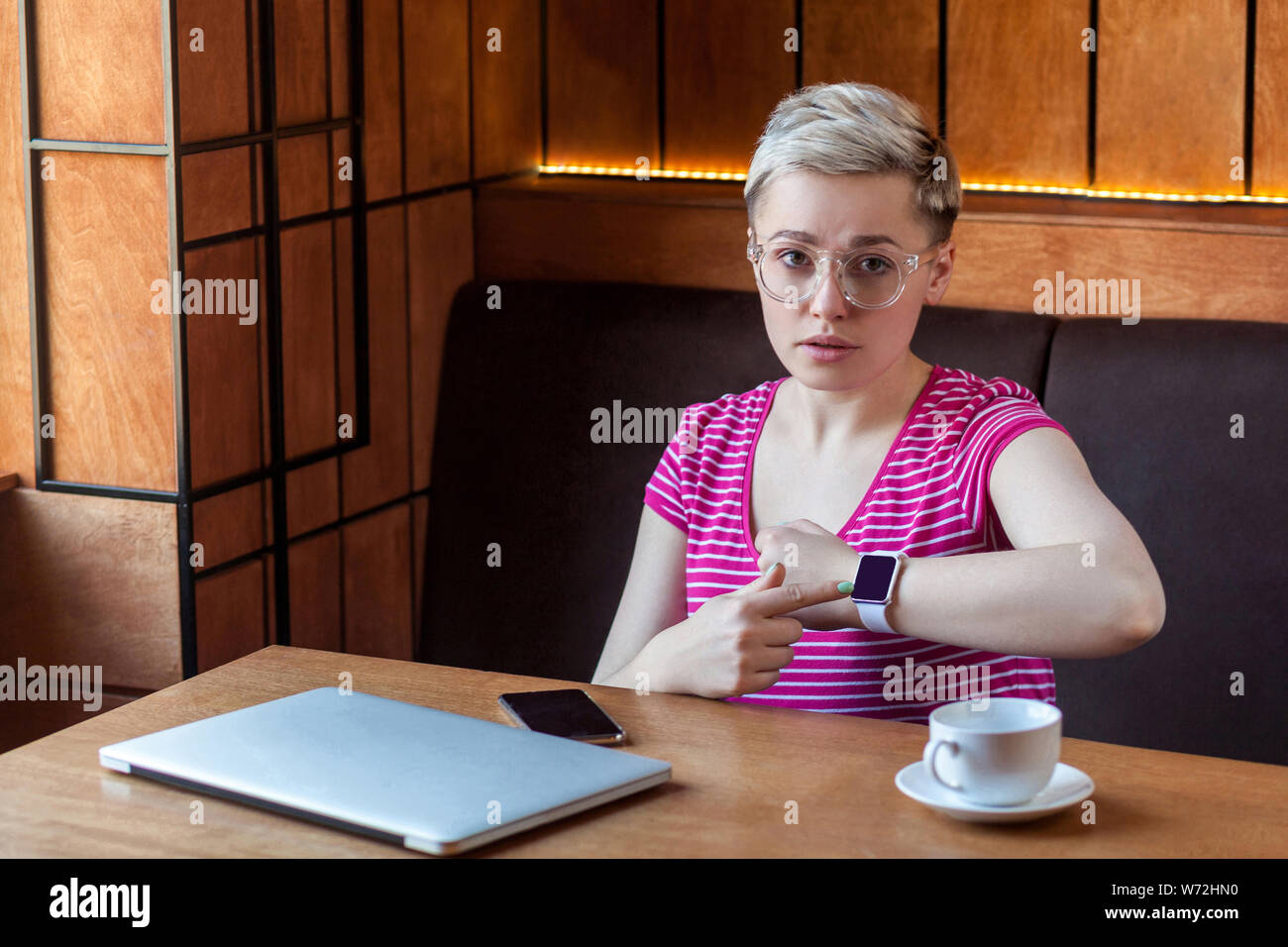 You late! Portrait of serious young bussineswoman with blonde short hair in pink t-shirt is sitting in cafe, pointing finger to wrist smart watch and Stock Photo