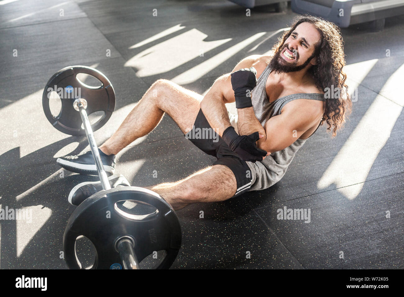 Portrait of grimace young adult man athlete with long curly hair working out in gym, sitting on floor and have strong hurt problem with elbow, injury Stock Photo