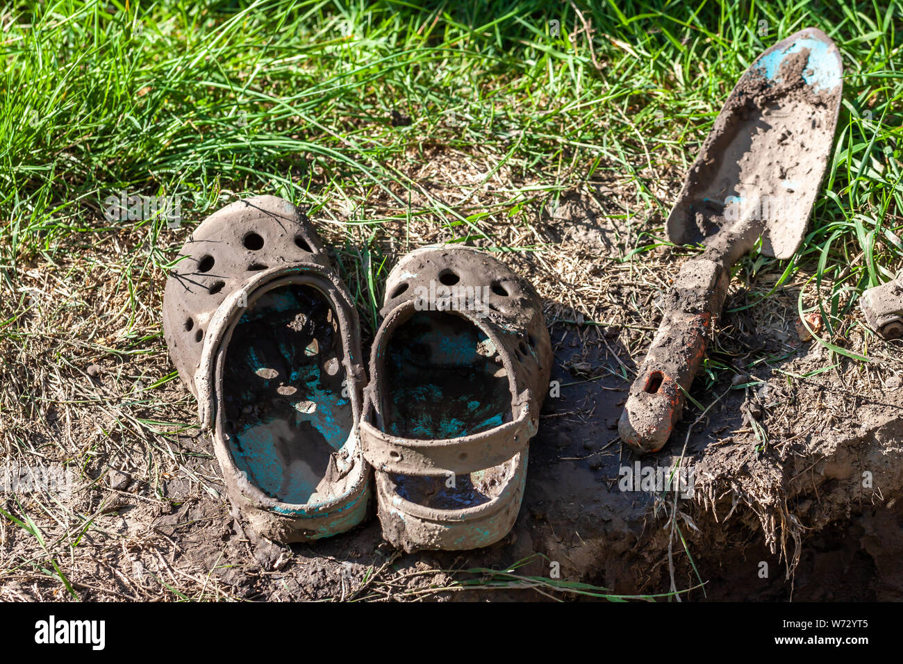 Garden clogs and shovel standing on the mud. Stock Photo
