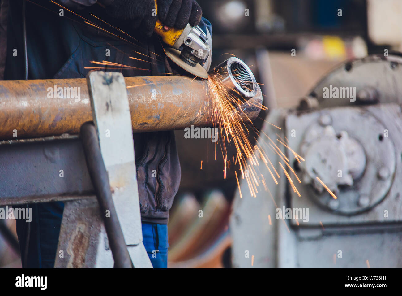Workers in a foundry grind castings with a grinding machine - Heavy industry workplace. Stock Photo