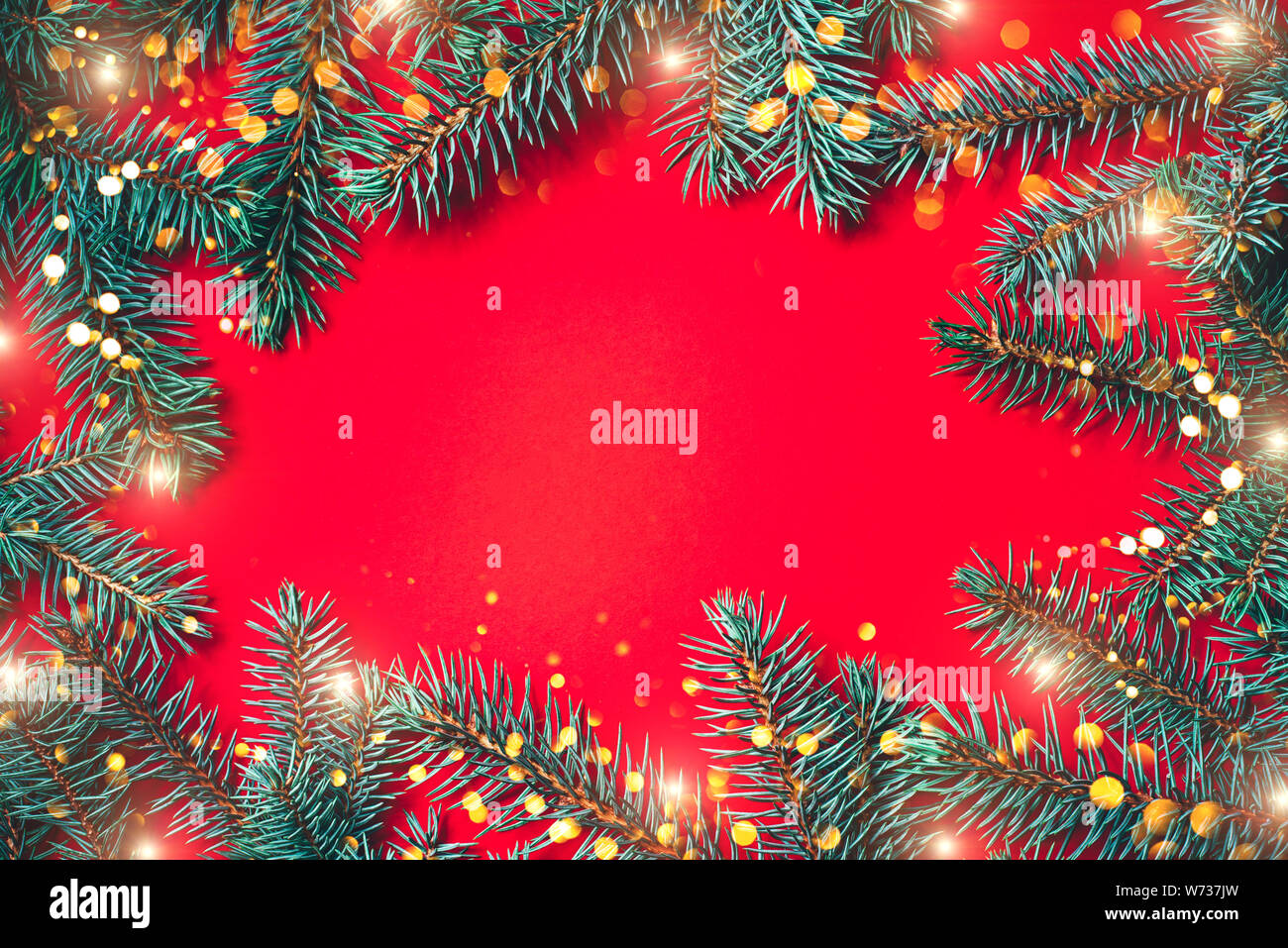 Fir Branches With Blurred Lights Garland On A Red Background