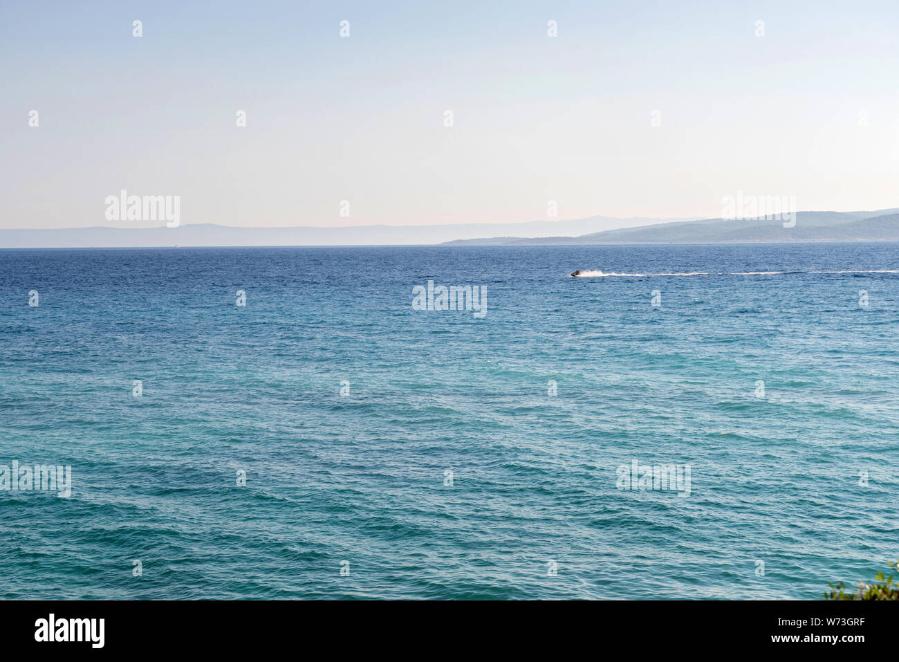 Croatian beach with blue sea and sailboat on horizon in Istria, Croatian coast Stock Photo