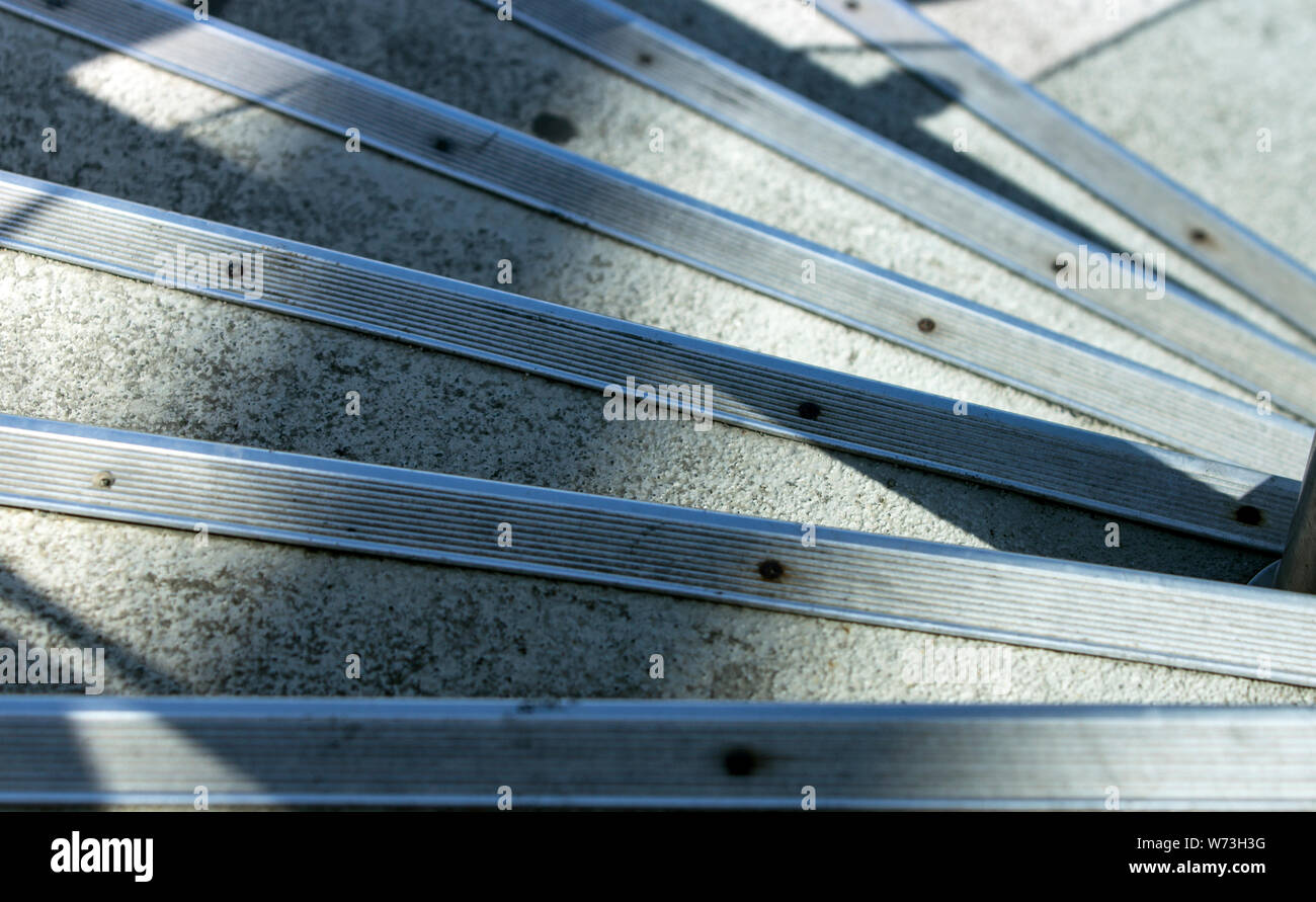 Close up high angle view of a series of concrete steps with protective metal bands at edges going down in a quarter spiral, under shadows and morning Stock Photo