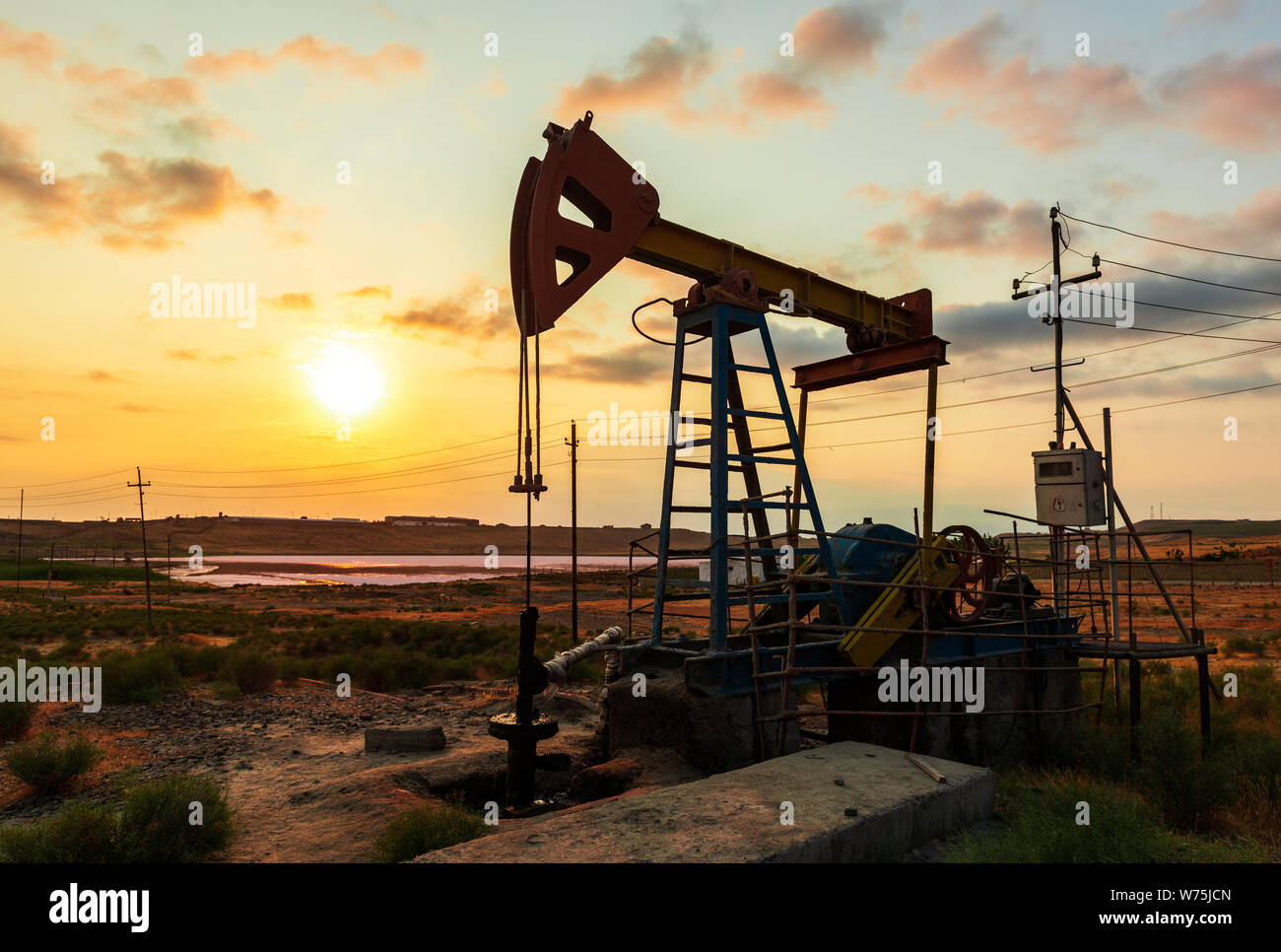 Oil rig pump against a colorful sunset sky Stock Photo