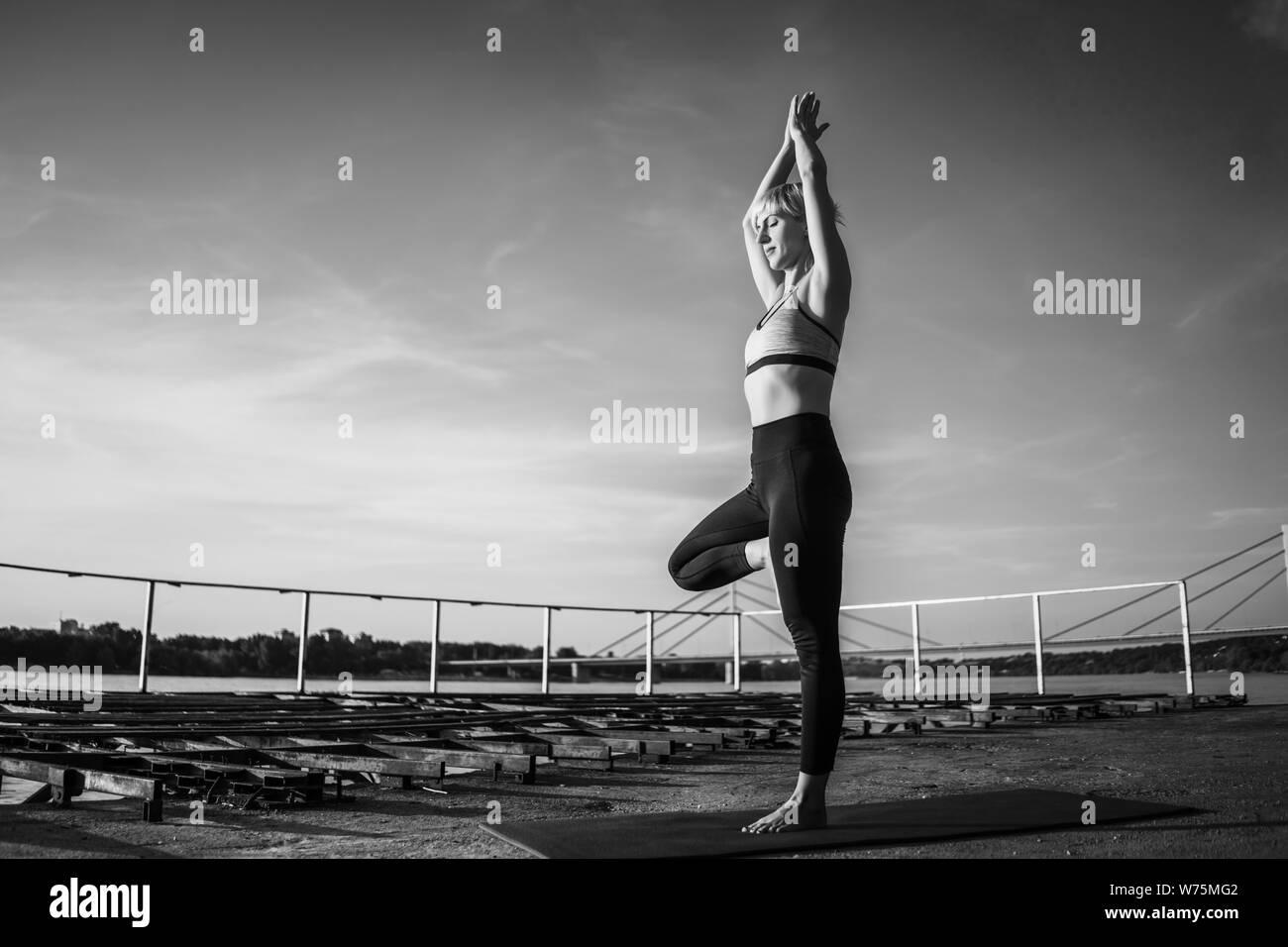 Woman practicing yoga on sunny day. Vriksasana, Tree pose Stock Photo