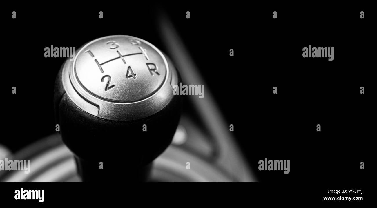 Close up view of a manual gear lever shift isolated on black background. Manual gearbox. Car interior details. Car transmission. Soft lighting. Abstra Stock Photo