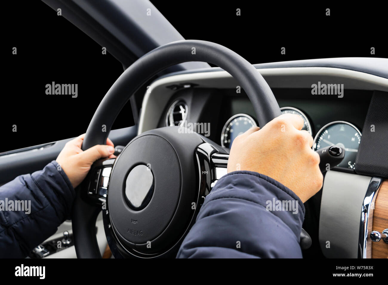 Male hands holding car steering wheel. Hands on steering wheel of a car driving. Young Man driving a car inside cabin. Multimedia system. Man Travelin Stock Photo