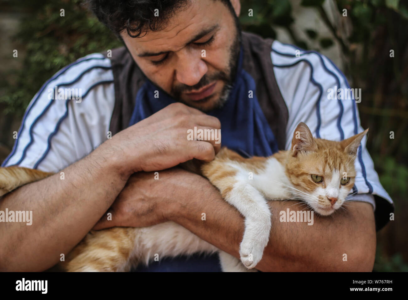 03 August 2019, Syria, Aleppo: Mohammed Alaa al-Jaleel, also known as 'the cat man of Aleppo' pets a cat at the Ernesto's Cat Sanctuary that he runs in Kafr Naya. During the Syrian war in 2012, Al-Jaleel was working as an ambulance driver in Aleppo, he used to drop off food for stray and abandoned cats on his way home after work. In 2015, he started to search for living cats in the war devastated areas and take them home, later in the year his compassionate work with cats gone viral and with the help of an Italian cat lover called Alessandra Abidin, he started to raise funds and receive donati Stock Photo