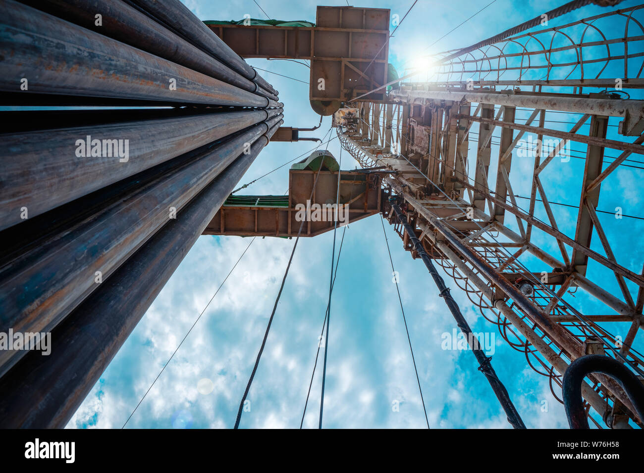 Oil and Gas Drilling Rig onshore dessert with dramatic cloudscape. Oil drilling rig operation on the oil platform in oil and gas industry. Stock Photo