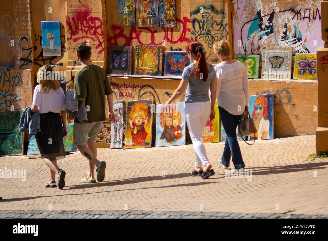 Kiev, Ukraine - May 19, 2019: People pass near paintings sold by artists on St. Andrew Descent Stock Photo