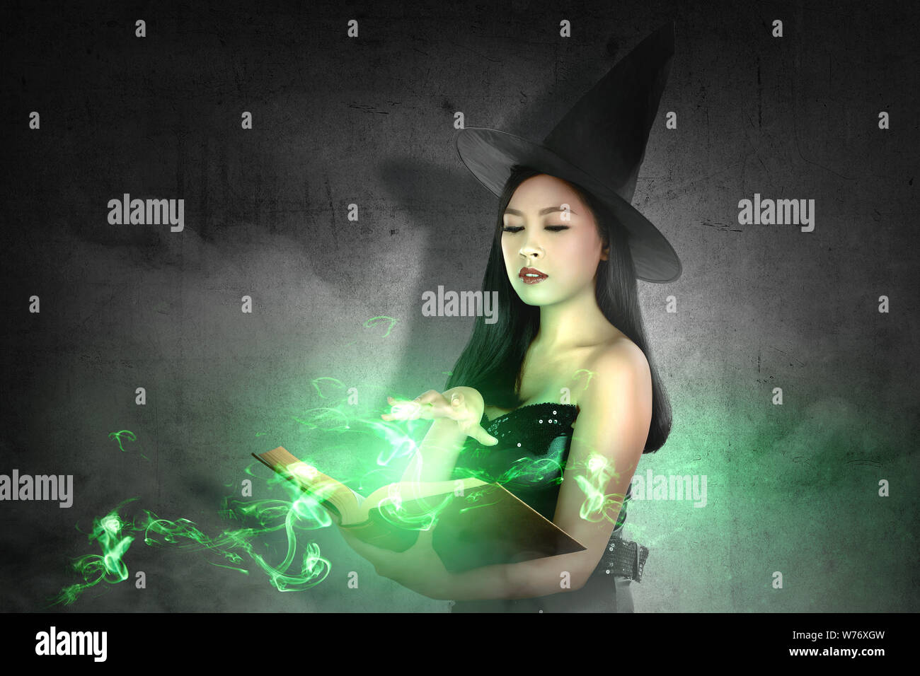 Asian witch woman in hat learns the spell from the magic book with a black wall background. Halloween concept Stock Photo