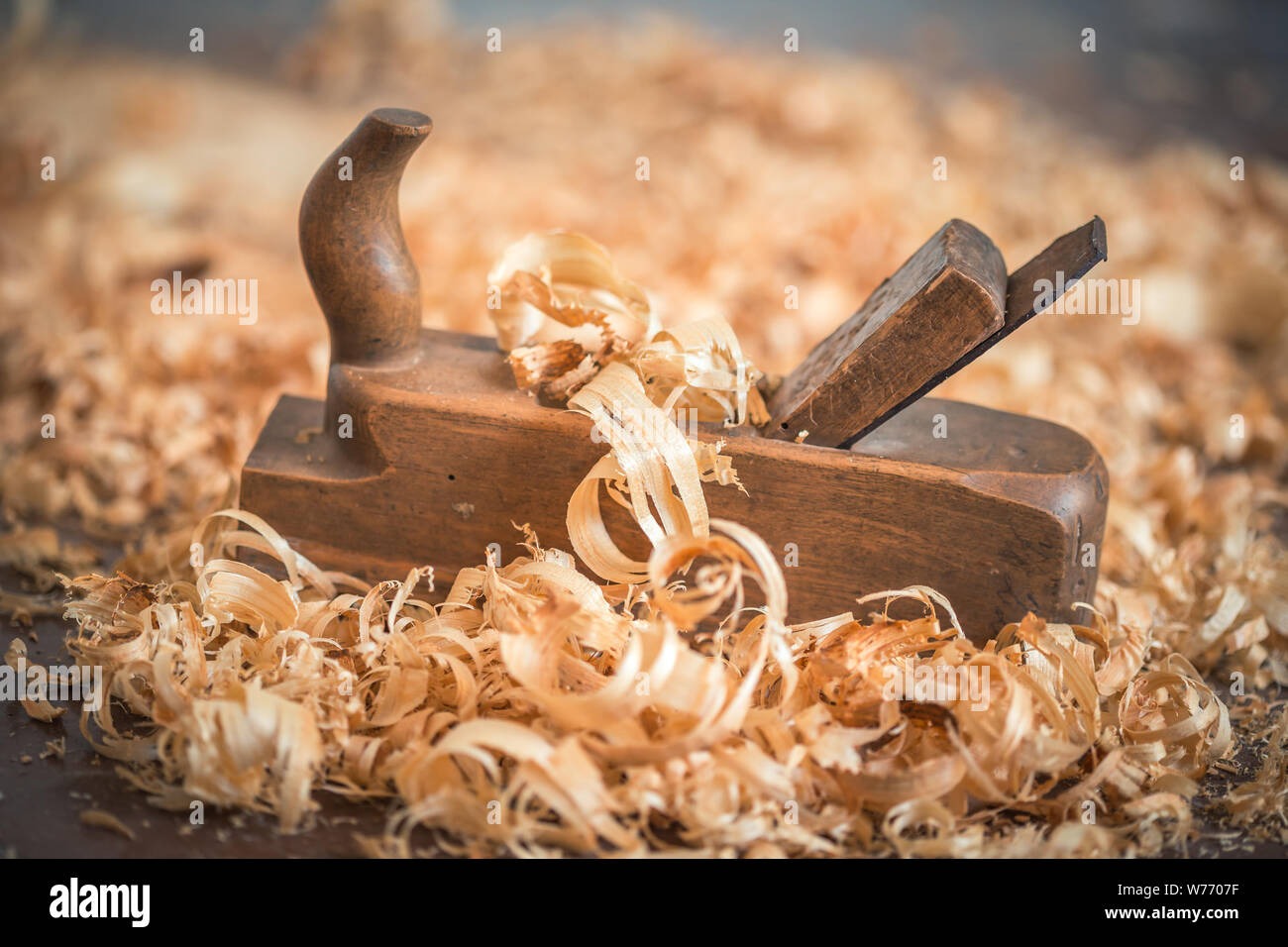 Old wooden hand plane for woodworking with wood shavings. Stock Photo