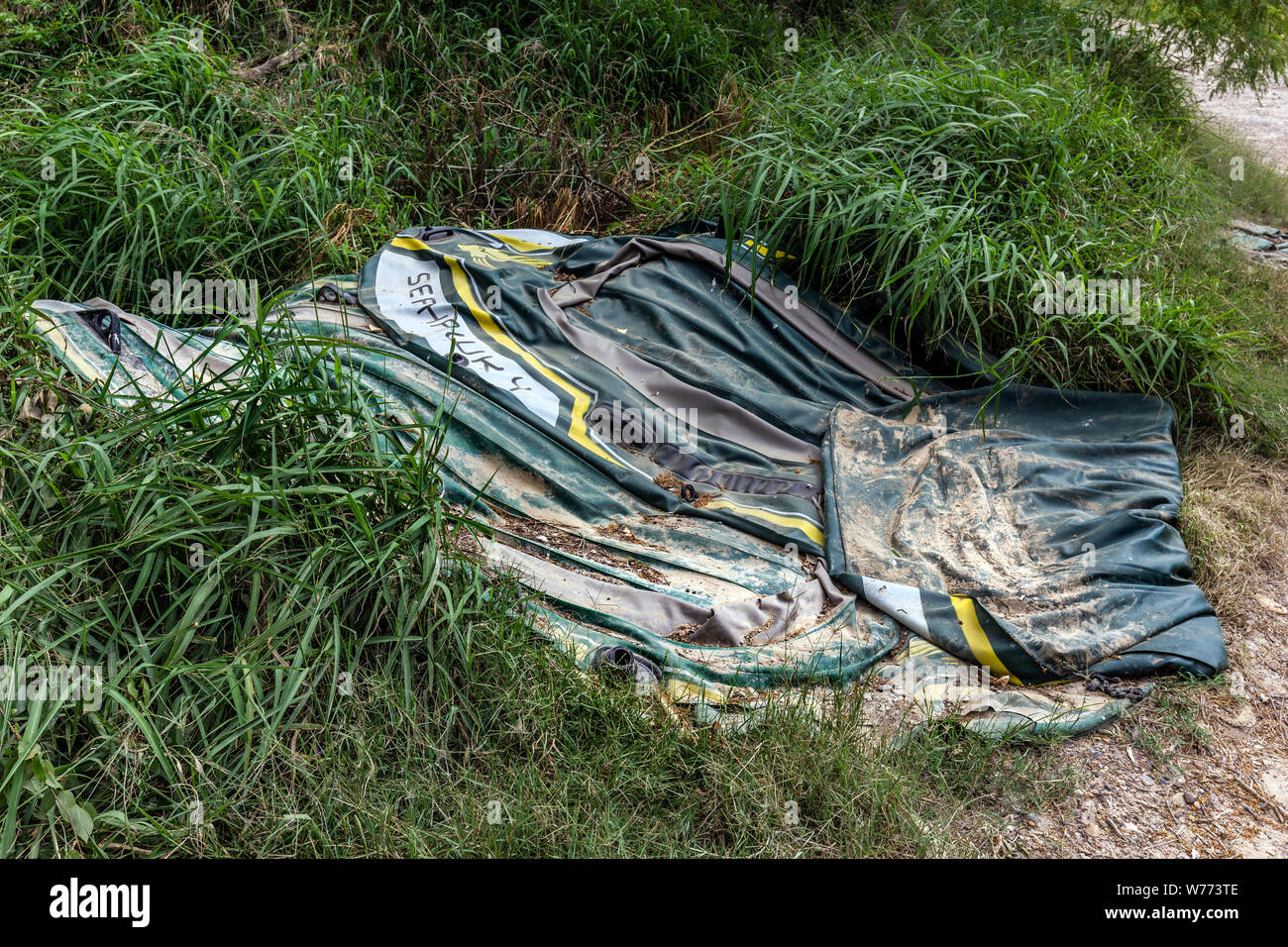 Discarded rafts used by migrants to cross the Rio Grande River  can be found on the shore of the Rio Grande, Roma, Texas, USA. Stock Photo