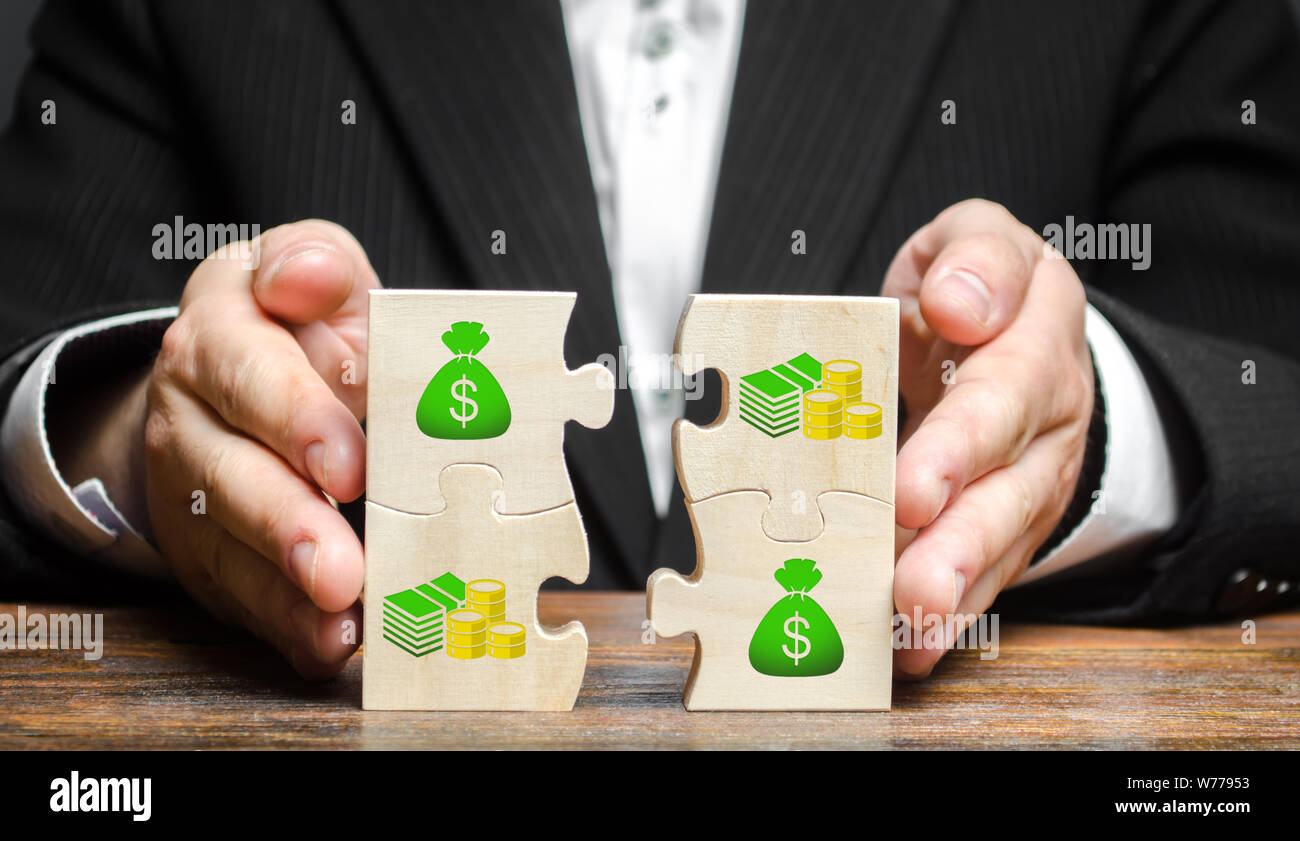 Businessman combines money puzzles. Fundraising, attracting investments for the implementation of business projects and startups. Crowdfunding. Accumu Stock Photo