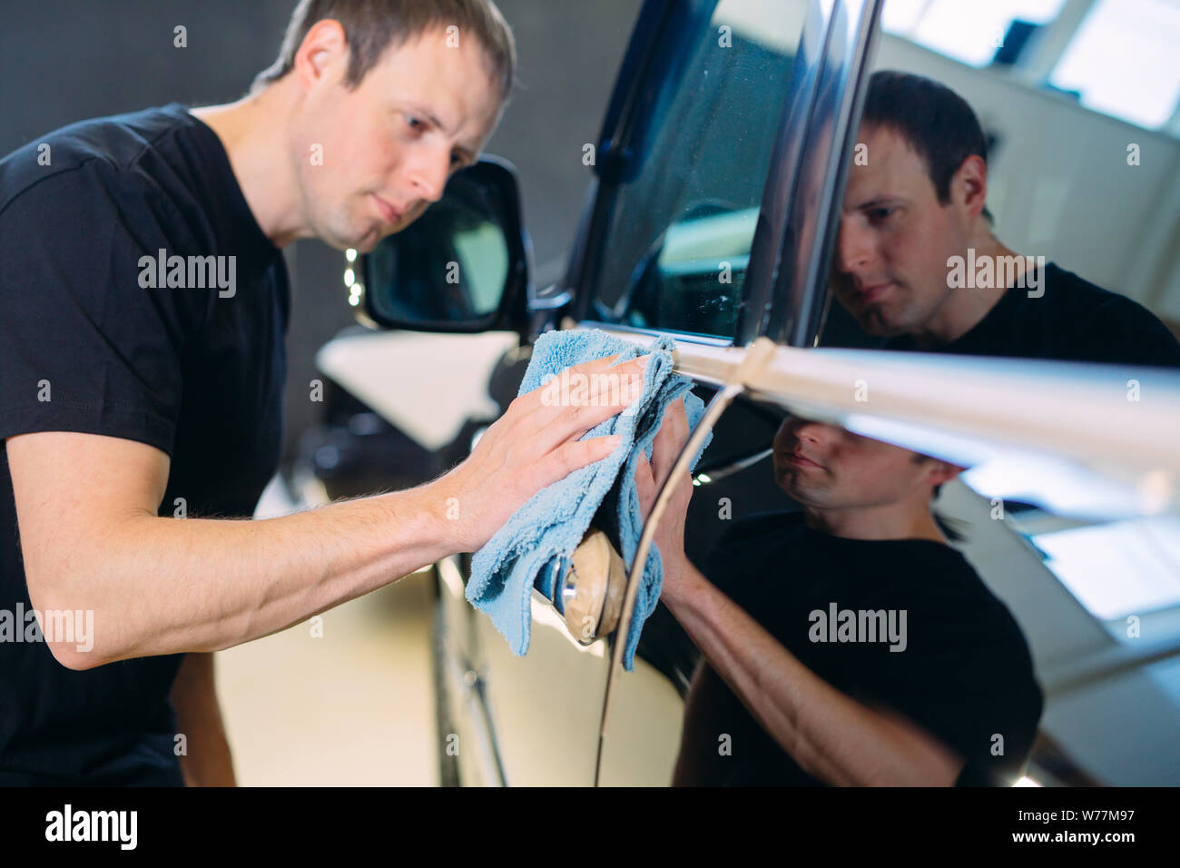 The man is wiping with a cloth body of a brilliant car. Stock Photo