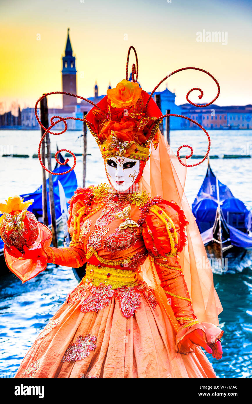 Carnival of Venice, beautiful mask at Piazza San Marco with gondolas and Grand Canal, Venezia, Italy. Stock Photo